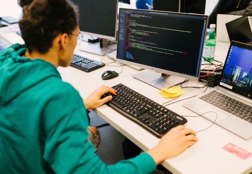 Etudiant bachelor numérique en train de coder sur son ordinateur