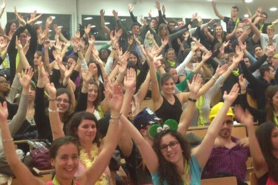 Header - Amphi plein d'étudiants les bras en l'air et souriants