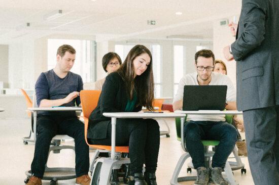 header - jeunes étudiants en salle de coworking suivant un cours concentrés