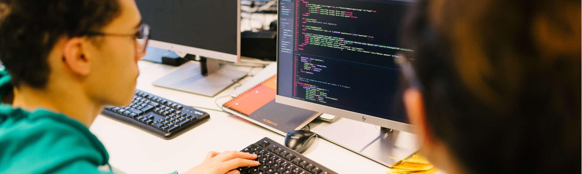 header - etudiant numerique en train de coder sur un ordinateur